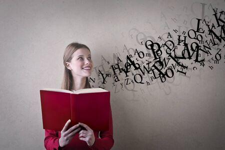 Girl is reading a red book Reklamní fotografie
