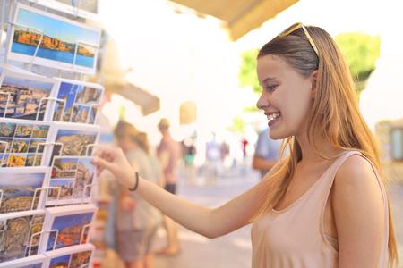 Nice girl is buying postcards photo