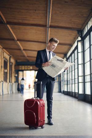 Geschäftsmann mit einem Koffer und einer Zeitung