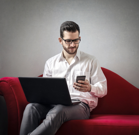empty: Man is working on the red sofa Stock Photo