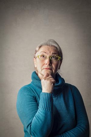Oude dame denkt Stockfoto