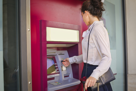 Girl is getting money from the ATM Foto de archivo