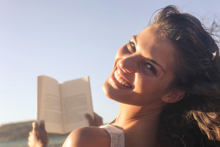 face to face: Pretty girl is reading in the sun Stock Photo