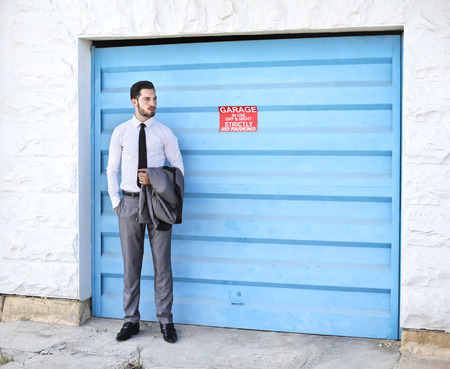 Businessman at the blue garage door