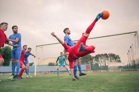 Jugar al fútbol en el campo Foto de archivo - 81646408