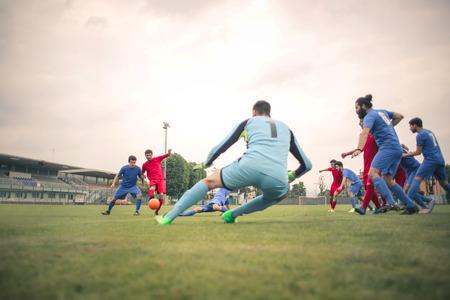 Fußball spielen auf dem Feld Standard-Bild