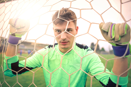 Soccer player in the net Stock Photo