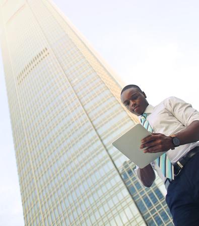 Geschäftsmann neben einem Wolkenkratzer Standard-Bild