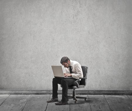 Arbeiten an einem Laptop sitzen auf einem Stuhl Lizenzfreie Bilder