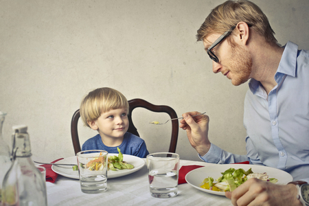 father with his child is eating photo