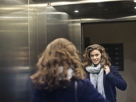 woman mirror: Woman in the elevator