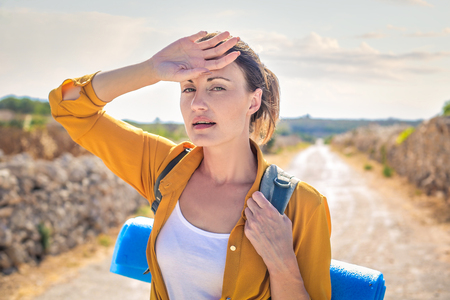 find: Woman is hiking in the sun Stock Photo