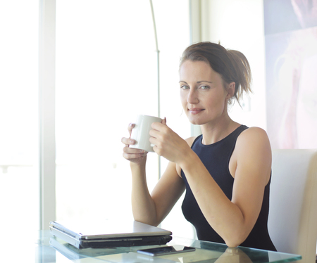 cup: Young business woman is drinking tea