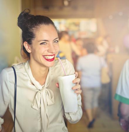 Happy lady is drinking the shake Фото со стока