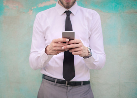 face to face: Businessman is typing on his phone Stock Photo