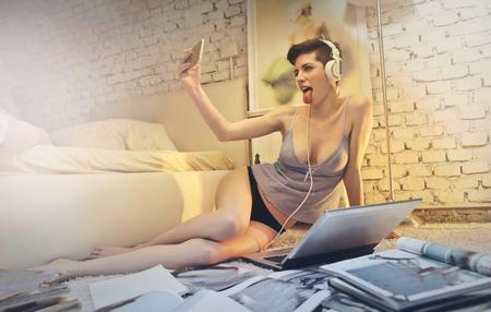 Vrouw in haar slaapkamer maakt ook een selfie Stockfoto