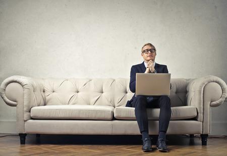 ビジネスマンはソファに座っています。 写真素材