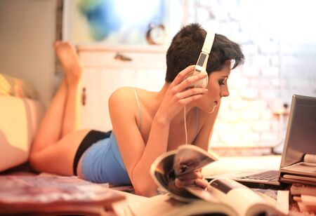 Woman is listening to music with a magazine photo