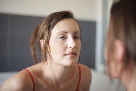 여자는 거울을보고있다. 스톡 콘텐츠