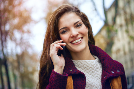 winter fashion: Woman on the phone is also smiling