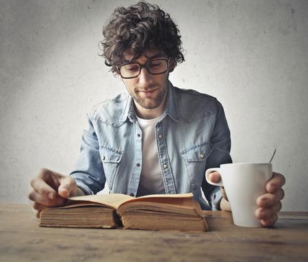 男の子は大きな本を読む、コーヒーを飲む