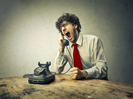 Businessman is screaming to the phone Stock Photo