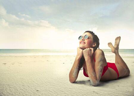 voyage: Une femme heureuse prend le soleil dans le sable