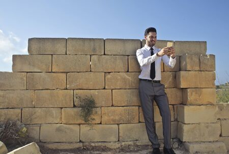 Businessman is taking a selfie at the wall photo