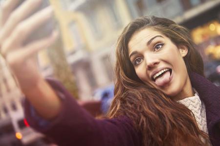 La ragazza divertente sta facendo un selfie