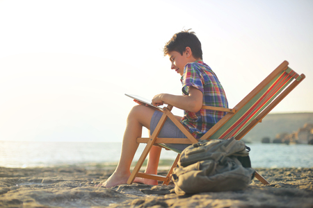Boy is relaxing at the beach after school