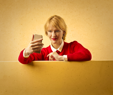 fashion: Blonde woman in a red sweater and her phone