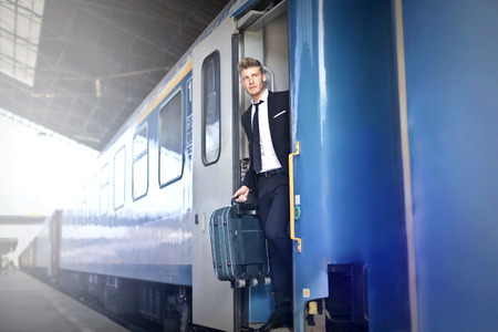 way out: Businessman is getting off the train Stock Photo