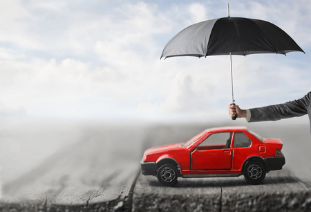 男は雨の中からあなたの車を保護します。