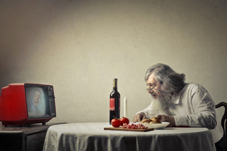 aged: Old man is eating dinner and watching tv Stock Photo