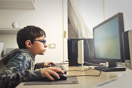 Young boy is playing on the computer 스톡 콘텐츠