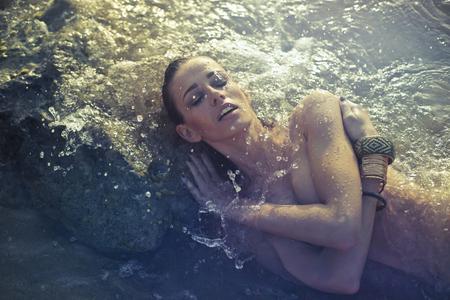 Donna nuda è sdraiata nell'acqua Archivio Fotografico - 80166564
