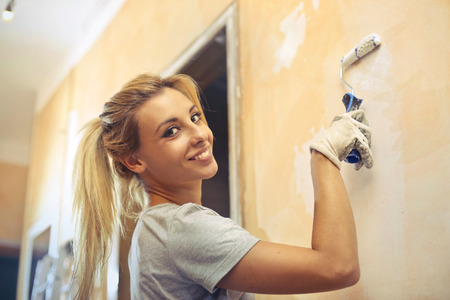 renew.: Young woman is painting the wall