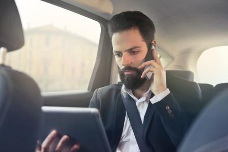 voyage: Businesman est au téléphone et regarde sa tablette
