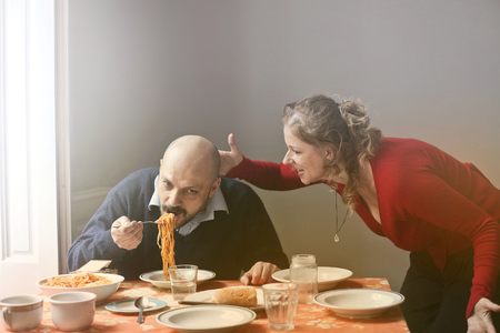 Angry woman screaming at a man who is eating spaghetti