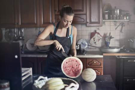 Girl opening watermelon in a kitchen
