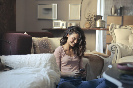 Happy girl using a smartphone in a living room Reklamní fotografie