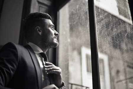 Businessman looking trough a window Imagens