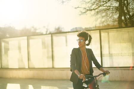 Girl with headphones riding a bike