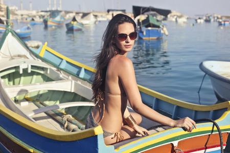 Young woman in bikini in a small boat