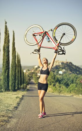 Sporty girl lifting a bike in the countryside