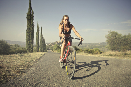 Girl cycling in a countryside road