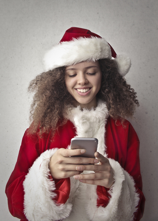 Portrait of a girl dressed as Santa Claus using a smartphone