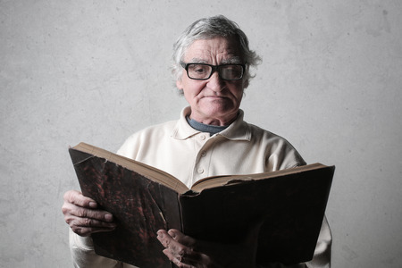 Aged man reading an old book Imagens