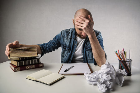 Desperate man sitting at a desk with books