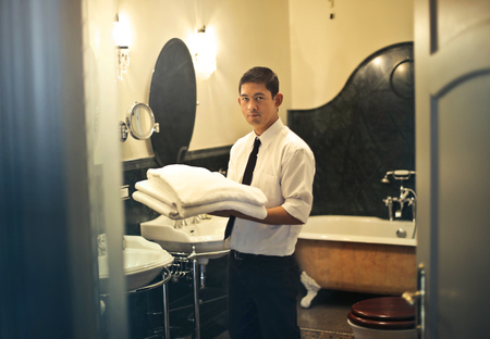Manservant at work in a hotel bathroom